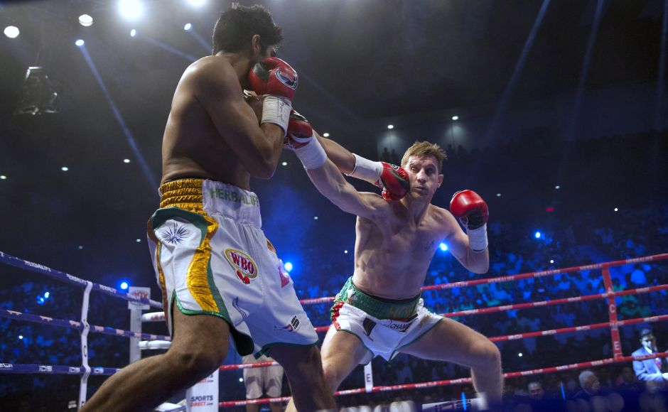 Indian boxer Vijender Singh, left, fight with Australia's Kerry Hope during their fight for the WBO Asia Pacific Super Middleweight title in New Delhi, India, Saturday, July 16, 2016. (AP Photo/Tsering Topgyal)
