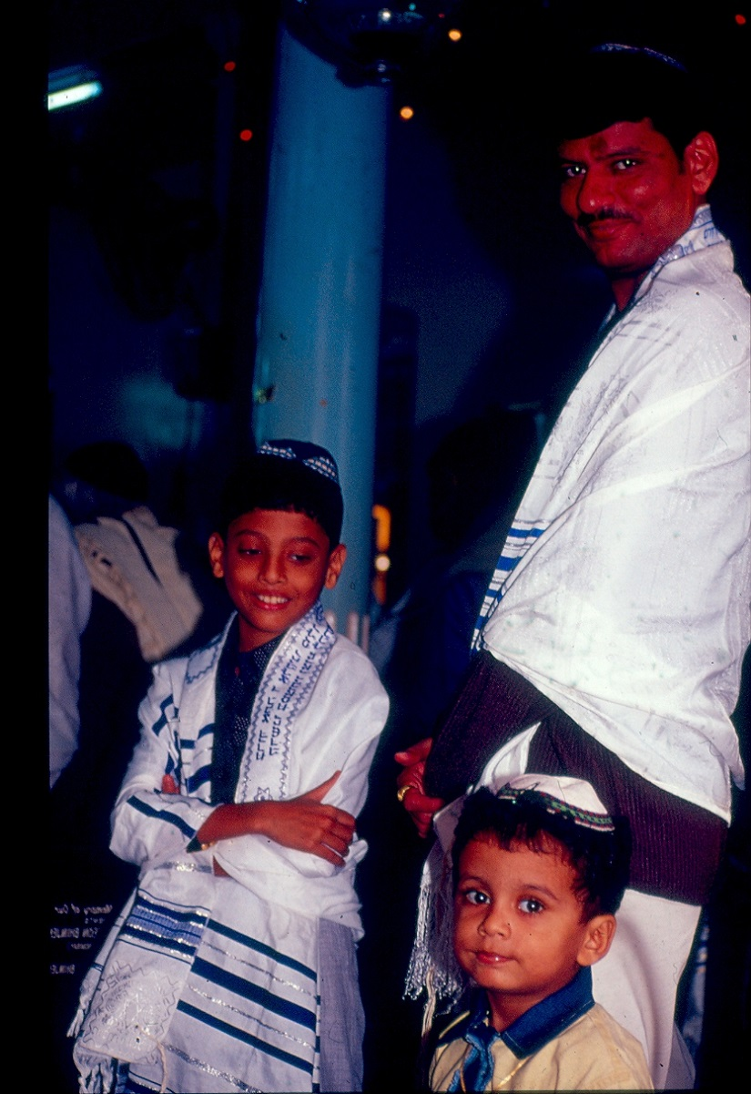 A Bene-Israel father with his two sons. It is evident that the older son has had his Bar Mitzvah (rite of initiation into the Jewish faith) because he has draped over his shoulders a prayer shawl, which means he can be counted as an adult Jewish male for the minyan (quorum of 10 Jewish men) necessary to conduct prayers in a synagogue. Image courtesy Jamshed Lentin