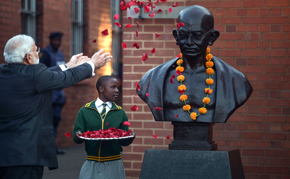 "Indian Prime Minister Narendra Modi (L) throws flowers on a sculpture in tribute to Indian independence hero Mahatma Gandhi, during his visit to the Constitutional Hill in Johannesburg on July 8, 2016, where Mahatma Gandhi and South African former president and liberation icon Nelson Mandela were kept in prison. Indian Prime Minister Narendra Modi took his Africa tour to South Africa on Friday, seeking to boost trade between two countries that he said ""shared values, suffering and struggles"". Among the countries' cultural and historic links is the 21 years that Mahatma Gandhi spent living in South Africa as a young lawyer and activist. / AFP"