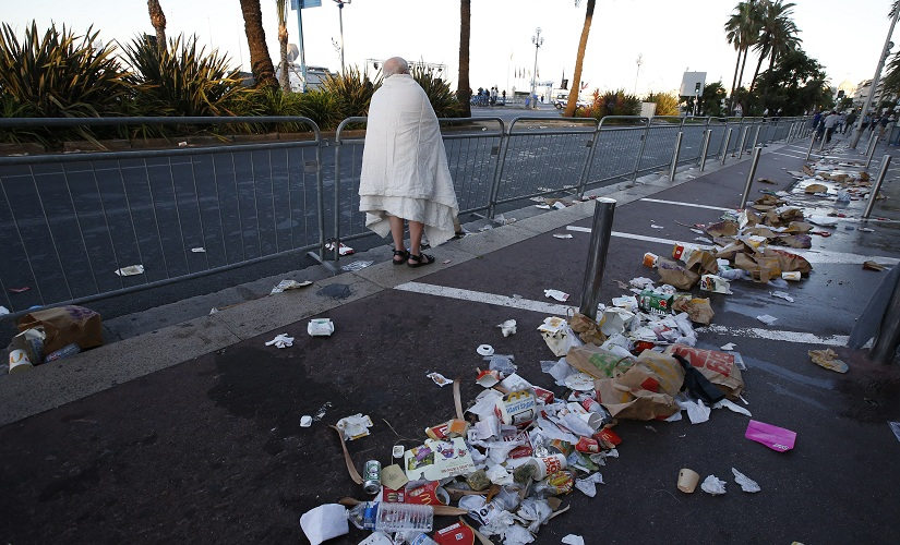 A man walks through debris scattered on the street, the day after the Nice attack. Reuters.