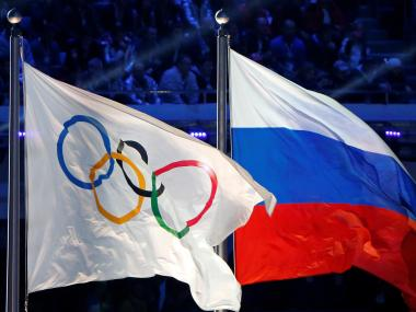 Russian flag (R) alongside the Olympic flag. Reuters