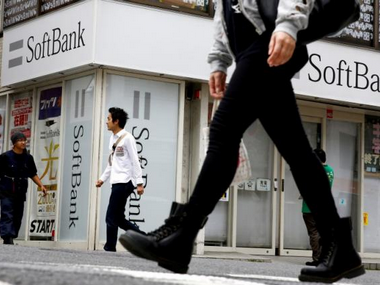 People walk past a retail shop of the SoftBank telecommunications company in Tokyo, Japan. Reuters