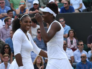 Venus Williams Serena Williams laugh together during their doubles match at Wimbledon.