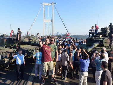People take selfies after soldiers involved in the coup surrendered on the Bosphorus Bridge in Istanbul, Turkey on 16 July 2016.  Reuters