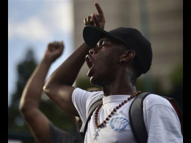 Demonstrators march through downtown Atlanta to protest the shootings of two black men by police officers on Friday. AP