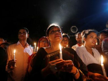 People attend a candle light vigil for the victims of the Dhaka attack. AP