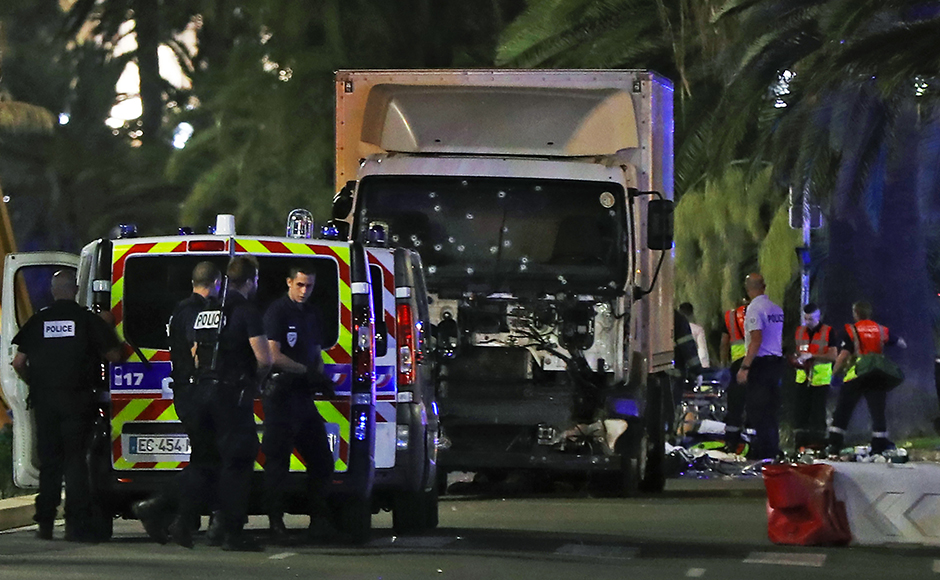 Police officers and rescue workers stand near a van that ploughed into a crowd leaving a fireworks display in the French Riviera town of Nice on July 14, 2016. The mayor of the French city of Nice said dozens of people were likely killed after a van rammed into a crowd marking Bastille Day in the French Riviera resort today and urged residents to stay indoors. / AFP PHOTO / VALERY HACHE