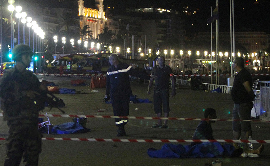 "Police officers, firefighters and rescue workers are seen at the site of an attack on the Promenade des Anglais on July 15, 2016, after a truck drove into a crowd watching a fireworks display in the French Riviera town of Nice. A truck ploughed into a crowd in the French resort of Nice on July 14, leaving at least 60 dead and scores injured in an ""attack"" after a Bastille Day fireworks display, prosecutors said on July 15. / AFP PHOTO / Valery HACHE"