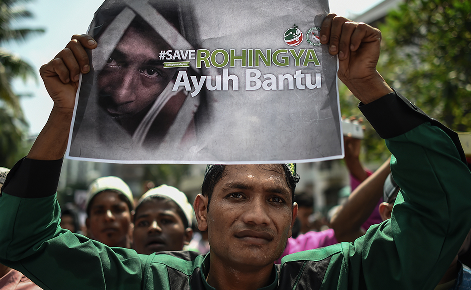 "A Myanmar ethnic Rohingya Muslim living in Malaysia displays a placard during a protest against the persecution of Rohingya Muslims in Myanmar, outside the Myanmar embassy in Kuala Lumpur on July 15, 2016. The European Parliament on July 8 urged Myanmar to end what it termed ""brutal repression"" and ""systematic persecution"" against the country's Rohingya Muslim minority. / AFP PHOTO / MOHD RASFAN"