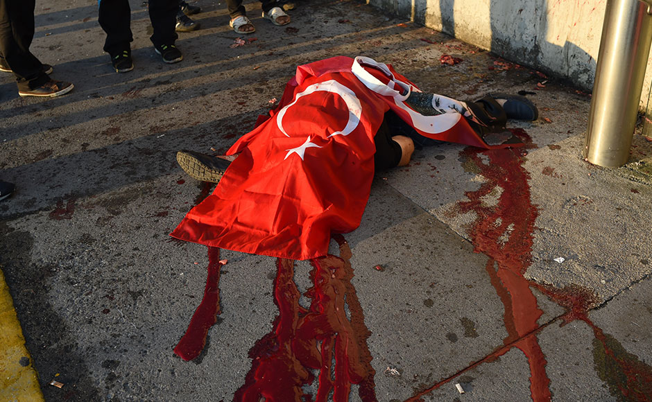 A civilian killed by Turkish soldiers lies on a ground on the Bosphorus bridge in Istanbul on July 16, 2016. At least 60 people have been killed and 336 detained in a night of violence across Turkey sparked when elements in the military staged an attempted coup, a senior Turkish official said. The majority of those killed were civilians and most of those detained are soldiers, said the official, without giving further details.