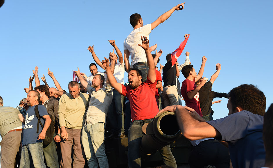 People react after they take over military position on the Bosphorus bridge in Istanbul on July 16, 2016. At least 60 people have been killed and 336 detained in a night of violence across Turkey sparked when elements in the military staged an attempted coup, a senior Turkish official said. The majority of those killed were civilians and most of those detained are soldiers, said the official, without giving further details.