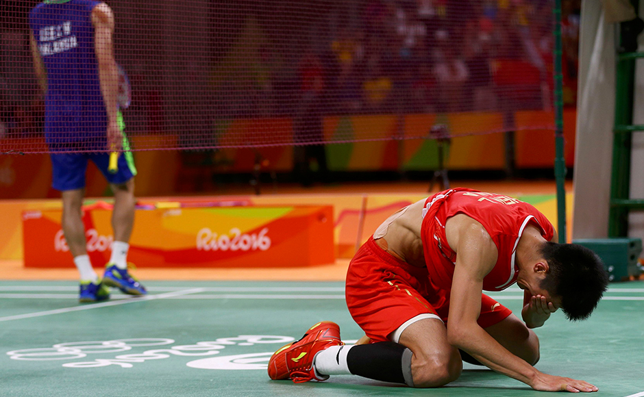 2016 Rio Olympics - Badminton - Men's Singles - Gold Medal Match - Riocentro - Pavilion 4 - Rio de Janeiro, Brazil - 20/08/2016. Chen Long (CHN) of China kneels on the court as he celebrates after winning his match against Chong Wei Lee (MAS) of Malaysia. REUTERS