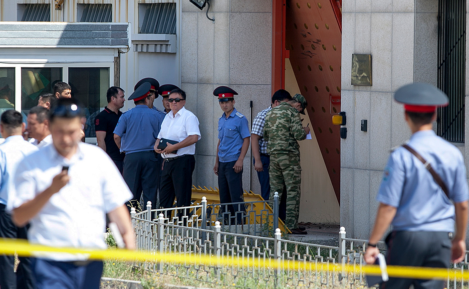 Kyrgyz police officers examine broken gates to the Chinese Embassy in Bishkek, Kyrgyzstan, Tuesday, Aug. 30, 2016. A suspected suicide bomber on Tuesday crashed a car through the entrance of the Chinese Embassy in the Kyrgyzstan capital of Bishkek, detonating a bomb that killed the attacker and wounded three embassy employees.AP