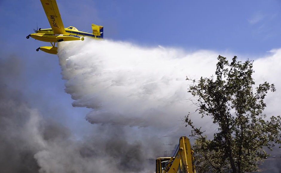 A fire fighting plane flies over a parking lot in Barragem da Povoa eastern Portugal Wednesday Aug. 3, 2016. The parking lot at open-air music and dance festival in eastern Portugal resembles a vehicle graveyard after a wildfire gutted 422 cars. Authorities said there were no casualties in the blaze that broke out Wednesday, forcing the evacuation of some 4,000 people at the festival. (Jose Manuel Costa via AP)