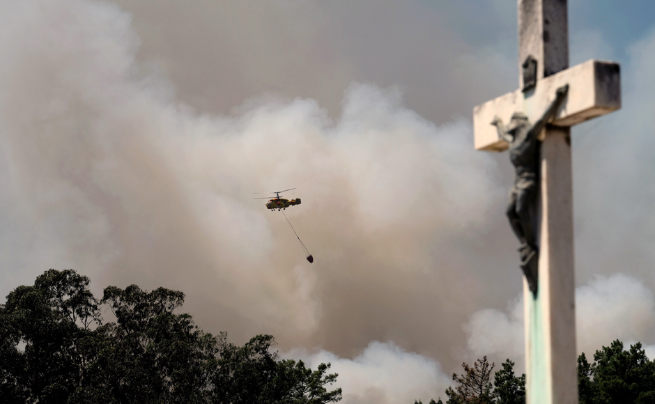 A firefighting helicopter flies over a forest fire near Mortagua, northern Portugal Thursday, Aug. 11 2016. Firefighters in Portugal are battling multiple blazes fed by brush in a hot, dry summer for a sixth straight day. Major fires have also been raging in northwestern Spain and southern France. AP