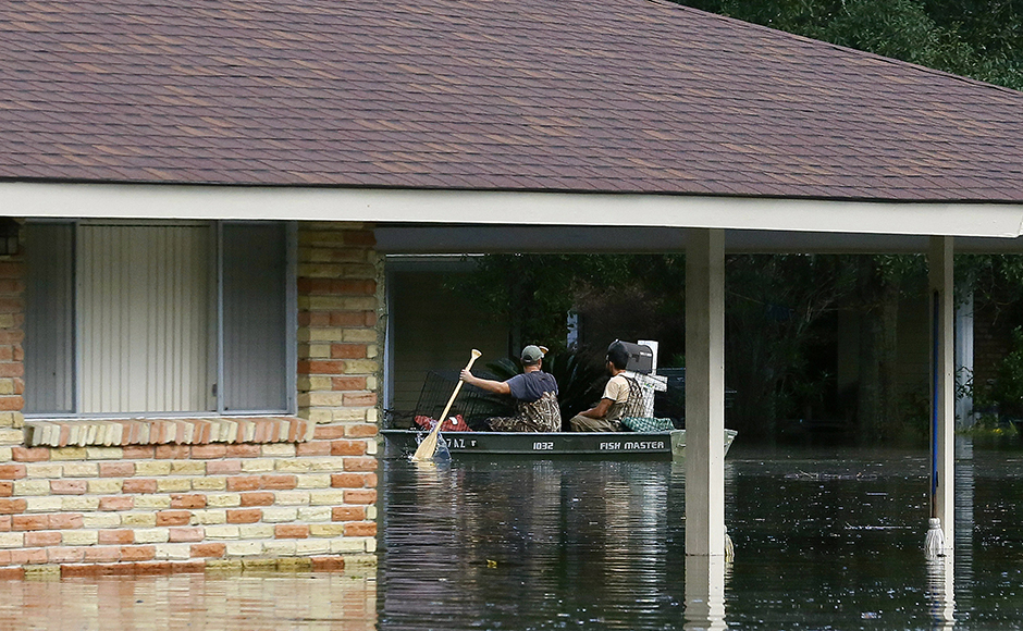 Residents use a boat to navigate through flood waters in Ascension Parish, Louisiana, U.S., August 15, 2016. REUTERS