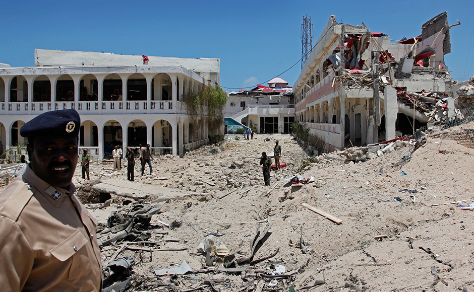 Somali soldiers stand near to a building destroyed by a blast near the presidential palace in the capital Mogadishu, Somalia Tuesday, Aug. 30, 2016. A suicide bomber has detonated an explosives-laden truck near the gate of Somalia's presidential palace in the capital on Tuesday, killing at least five people, police say.AP