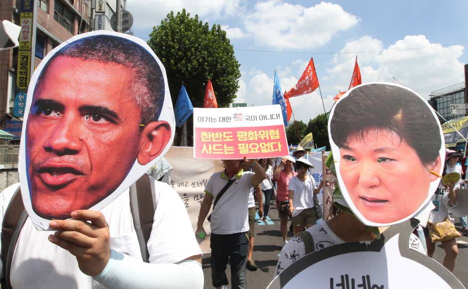 "South Korean protesters wearing masks of U.S. President Barack Obama and South Korean President Park Geun-hye, right, march to oppose a plan to deploy an advanced U.S. missile defense system called Terminal High-Altitude Area Defense, or THAAD, in Seoul, South Korea, Monday, Aug. 15, 2016. An advanced U.S. missile defense system will be deployed in a rural farming town in southeastern South Korea, Seoul officials announced last month, angering not only North Korea and China but also local residents who fear potential health hazards that they believe the U.S. system might cause. The sign at center reads "" No need THAAD in Korea Peninsular."" AP"