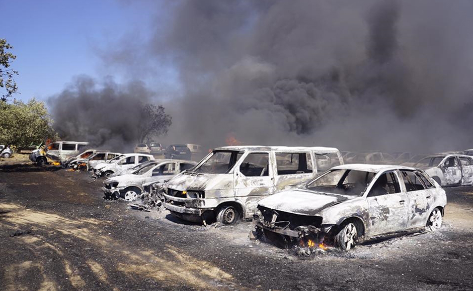 Burnt out vehicles stand in a parking lot in Barragem da Povoa eastern Portugal Wednesday Aug. 3, 2016. The parking lot at open-air music and dance festival in eastern Portugal resembles a vehicle graveyard after a wildfire gutted 422 cars. Authorities said there were no casualties in the blaze that broke out Wednesday, forcing the evacuation of some 4,000 people at the festival. (Jose Manuel Costa via AP)