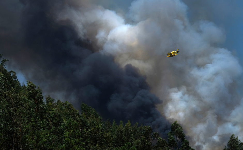 A firefighting airplane flies above a forest fire near Mortagua, northern Portugal Thursday, Aug. 11 2016. Firefighters in Portugal are battling multiple blazes fed by brush in a hot, dry summer for a sixth straight day. Major fires have also been raging in northwestern Spain and southern France. AP