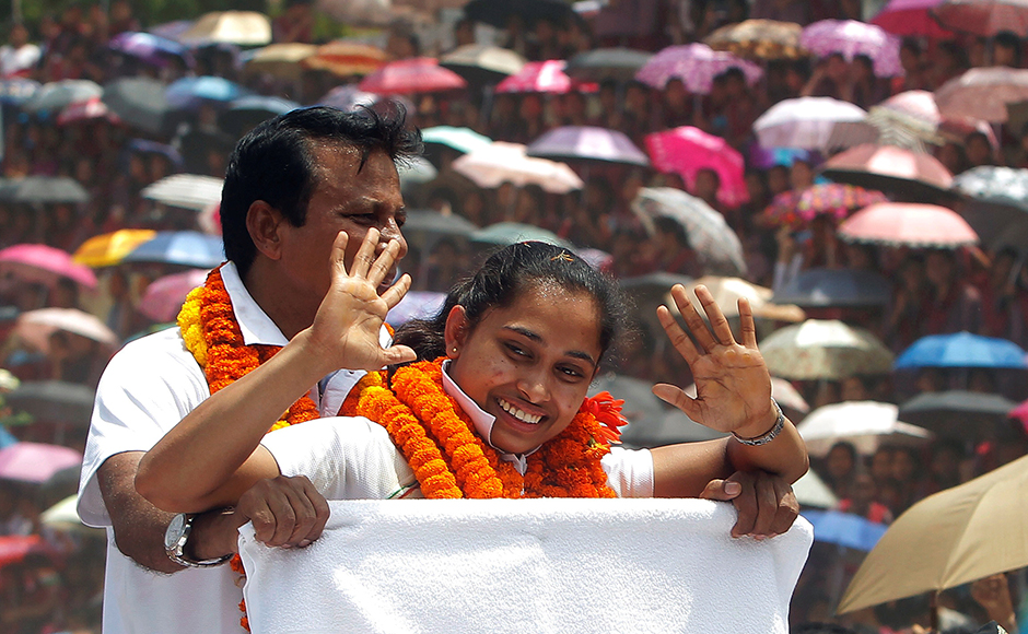 Gymnast Dipa Karmakar waves as she stands in a vehicle during her felicitation parade after her return from Rio Olympics, upon her arrival on the outskirts of Agartala, India, August 22, 2016. REUTERS