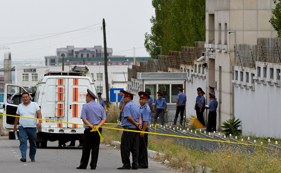 Emergency Ministry minivan is parked, as Kyrgyz police officers speak outside gates to the Chinese Embassy in Bishkek, Kyrgyzstan, Tuesday, Aug. 30, 2016. A suspected suicide bomber on Tuesday crashed a car through the entrance of the Chinese Embassy in the Kyrgyzstan capital of Bishkek, detonating a bomb that killed the attacker and wounded embassy employees.AP