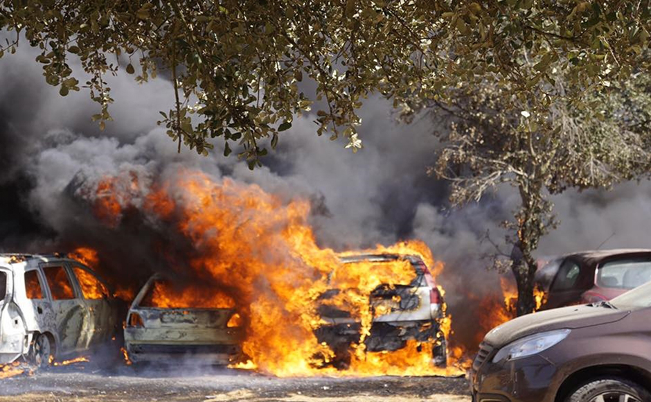 Cars burn in a parking lot in Barragem da Povoa eastern Portugal Wednesday Aug. 3, 2016. The parking lot at open-air music and dance festival in eastern Portugal resembles a vehicle graveyard after a wildfire gutted 422 cars. Authorities said there were no casualties in the blaze that broke out Wednesday, forcing the evacuation of some 4,000 people at the festival. (Jose Manuel Costa via AP)