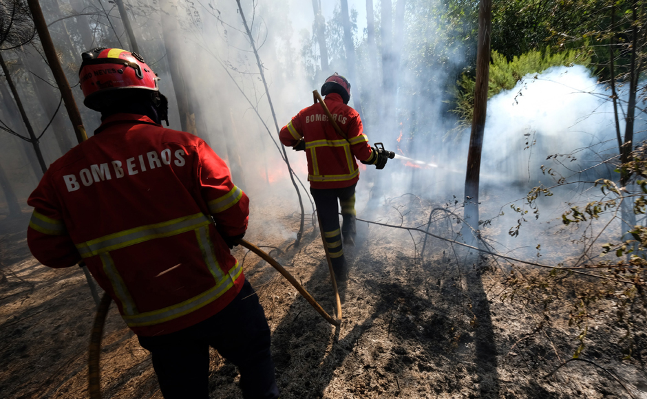 Firefighters battle a forest fire, near Mealhada, northern Portugal Thursday, Aug. 11 2016. Firefighters in Portugal are battling multiple blazes fed by brush in a hot, dry summer for a sixth straight day. Major fires have also been raging in northwestern Spain and southern France. AP