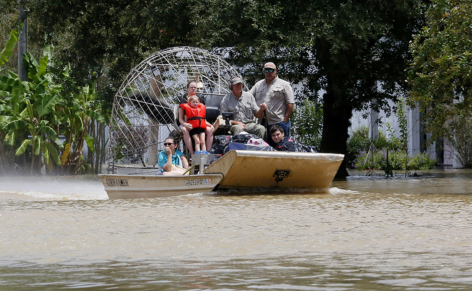 An airboat brings rescued residents to safety in Ascension Parish, Louisiana, U.S., August 15, 2016. REUTERS