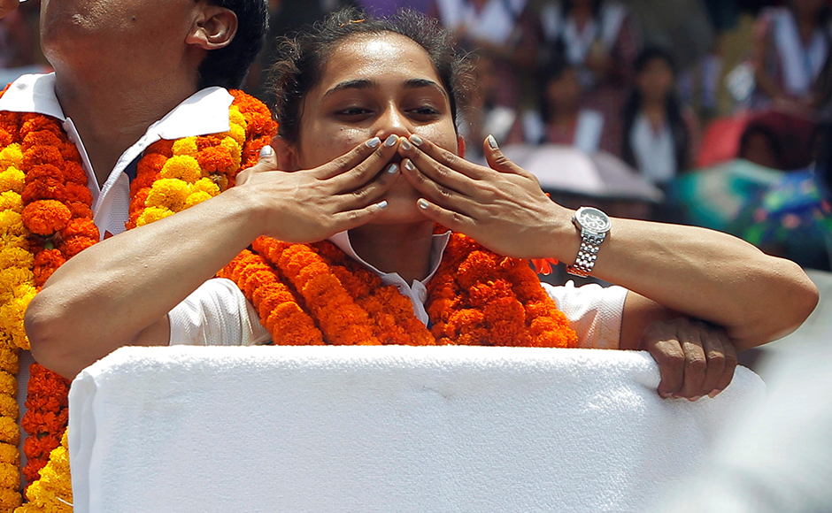 Gymnast Dipa Karmakar gestures as she stands in a vehicle during her felicitation parade after her return from Rio Olympics, upon her arrival on the outskirts of Agartala, India, August 22, 2016. REUTERS