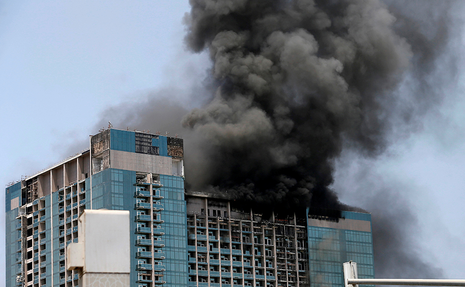 Thick black smoke billowed from the top 20 floors of the almost-completed commercial building in the UAE's capital and firefighters, overseen by helicopters, were working to put the blaze out two hours after it started. Reuters