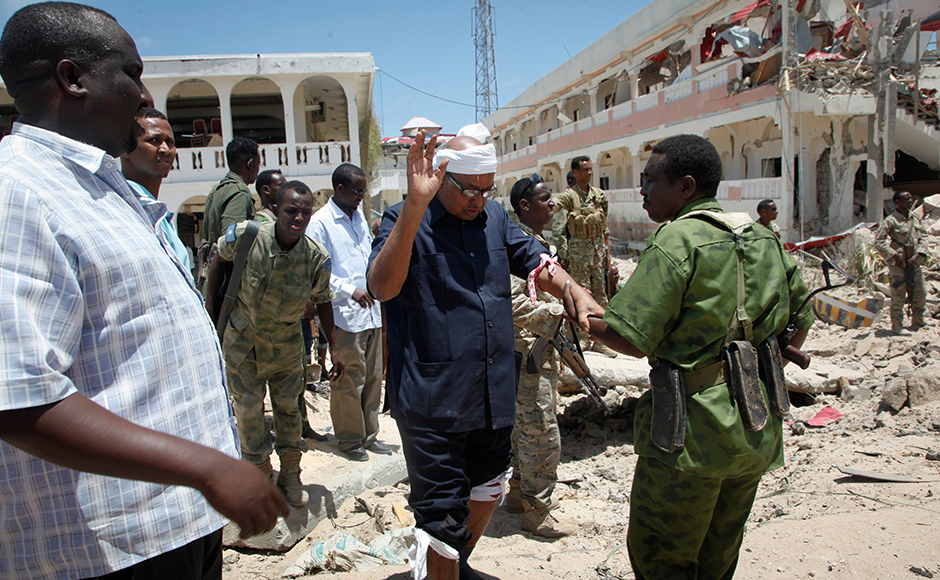 A soldier helps Somali lawmaker Abdalla Bos Ahmed, center, after he was injured by a blast near the presidential palace in the capital Mogadishu, Somalia Tuesday, Aug. 30, 2016. A suicide bomber has detonated an explosives-laden truck near the gate of Somalia's presidential palace in the capital on Tuesday, killing at least five people, police say.AP