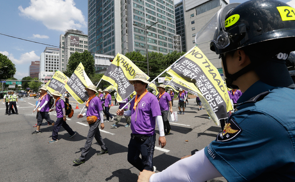 "South Korean protesters march to oppose a plan to deploy an advanced U.S. missile defense system called Terminal High-Altitude Area Defense, or THAAD, in Seoul, South Korea, Monday, Aug. 15, 2016. An advanced U.S. missile defense system will be deployed in a rural farming town in southeastern South Korea, Seoul officials announced last month, angering not only North Korea and China but also local residents who fear potential health hazards that they believe the U.S. system might cause. The letters on flags read "" No need THAAD in Korea Peninsular."" AP"