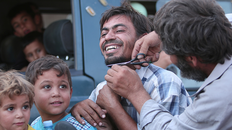 A man cuts the beard of a civilian who was evacuated with others by the Syria Democratic Forces (SDF) fighters from an Islamic State-controlled neighbourhood of Manbij, in Aleppo Governorate, Syria, August 12, 2016. The SDF has said Islamic State was using civilians as human shields. REUTERS/Rodi Said - RTSMZEB