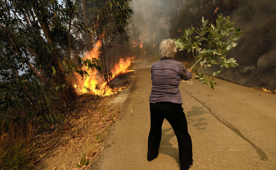 A woman uses a tree branch to fight a fire on the road leading to the village of Parada, near Mortagua, northern Portugal, Thursday, Aug. 11 2016. Firefighters in Portugal are battling multiple blazes fed by brush in a hot, dry summer for a sixth straight day. Major fires have also been raging in northwestern Spain and southern France. AP