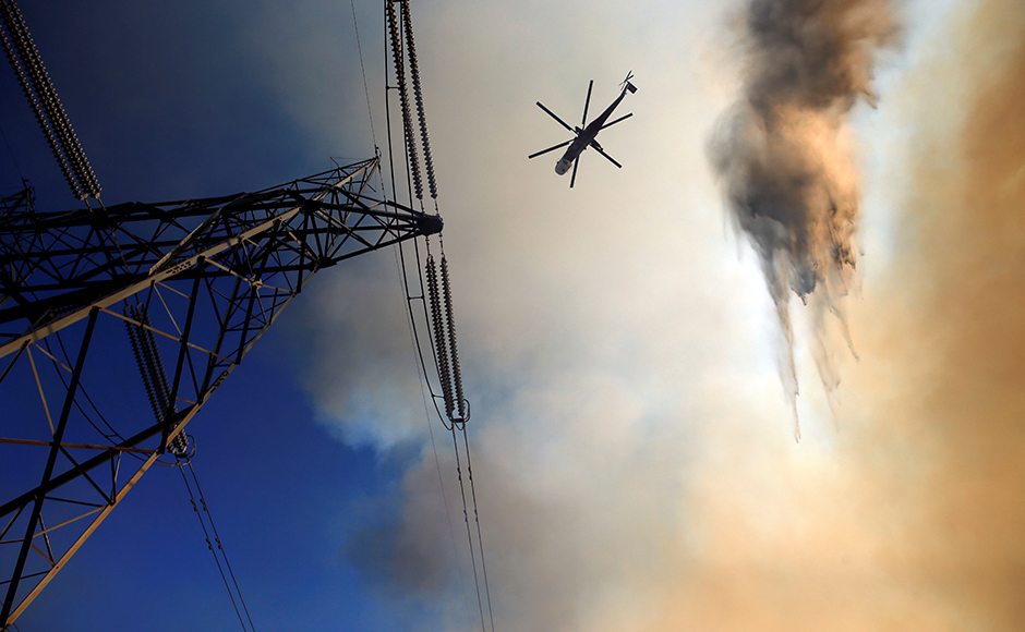 Firefighters described the blaze as unusually fierce, even for a year of intense wildfires in the US West, where years of drought have placed a heavy burden on firefighting resources. A firefighting helicopter maneuvers around power lines and smoke to make a water drop during the fire. Reuters