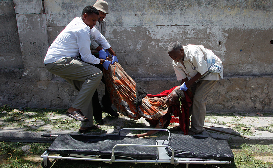 Somali men carry away the body of a woman who was killed by a blast near the presidential palace in the capital Mogadishu, Somalia Tuesday, Aug. 30, 2016. A suicide bomber has detonated an explosives-laden truck near the gate of Somalia's presidential palace in the capital on Tuesday, killing at least five people, police say.AP