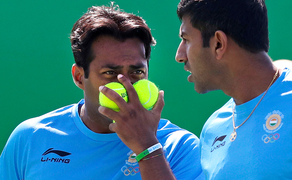 Leander Paes, of India, blocks his face with tennis balls as he talks with his partner Rohan Bopanna, right, during their match at the 2016 Summer Olympics in Rio de Janeiro, Brazil, Saturday, Aug. 6, 2016. Paes and Bopanna lost their first round match to Poland's Lukasz Kubot and Marcin Matkowski. (AP Photo/Charles Krupa)