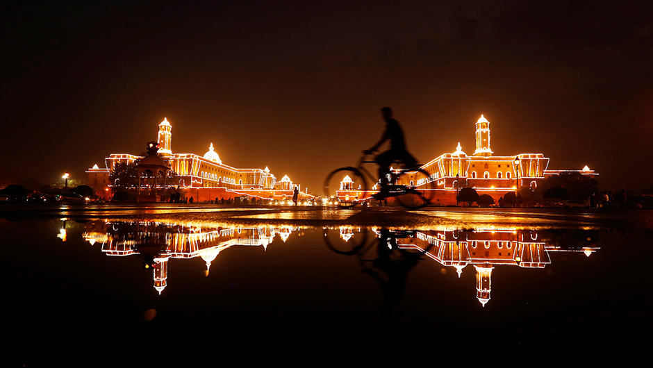 A cyclist rides past the Illuminated Indian Defence Ministry (L), Presidential Palace (C) and Home Ministry ahead of Indiaís Independence Day celebrations in New Delhi, India, August 13, 2016. REUTERS/Adnan Abidi - RTX2KJQH