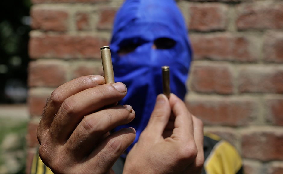 A masked Kashmiri youth shows empty bullet cartridges allegedly fired by government forces at the four civilians at Aripanthan village in Srinagar. More than 7000 civilians have also been injured in action by government forces hundreds of them have lost eyesight and others maimed for life due to firearm injuries. AP