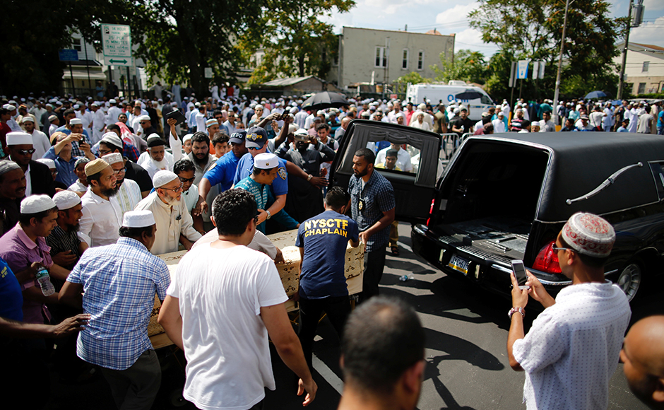 "A crowd of community members move the coffin to the hearse as they gather for the funeral service of the Imam. The police charged Morel, 35, with two counts of second-degree murder. ""There is nothing in the preliminary investigation to indicate that they were targeted because of their faith,"" police told journalists. Reuters"