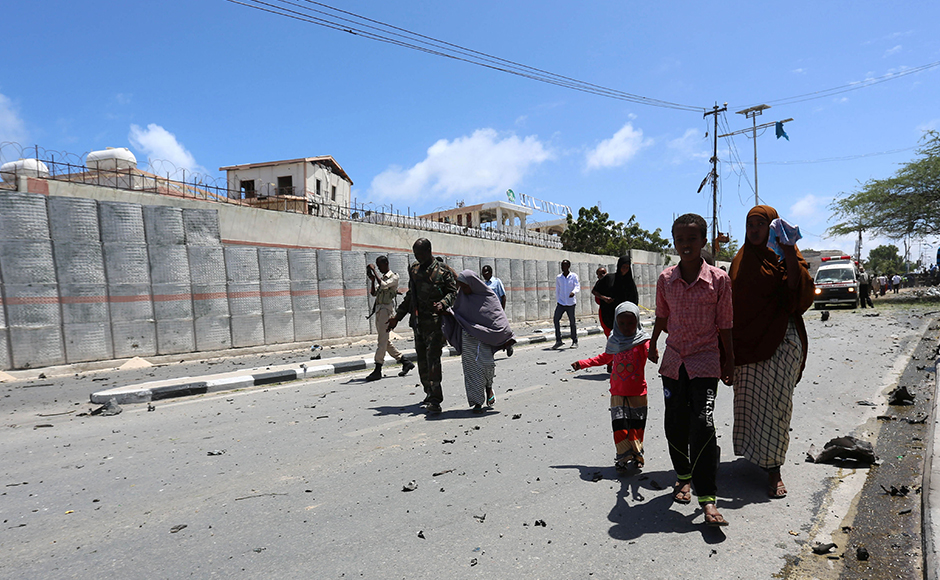 Somali security forces escort civilians following a car bomb claimed by al Shabaab Islamist militants outside the president's palace in the Somali capital of Mogadishu, August 30, 2016. Reuters