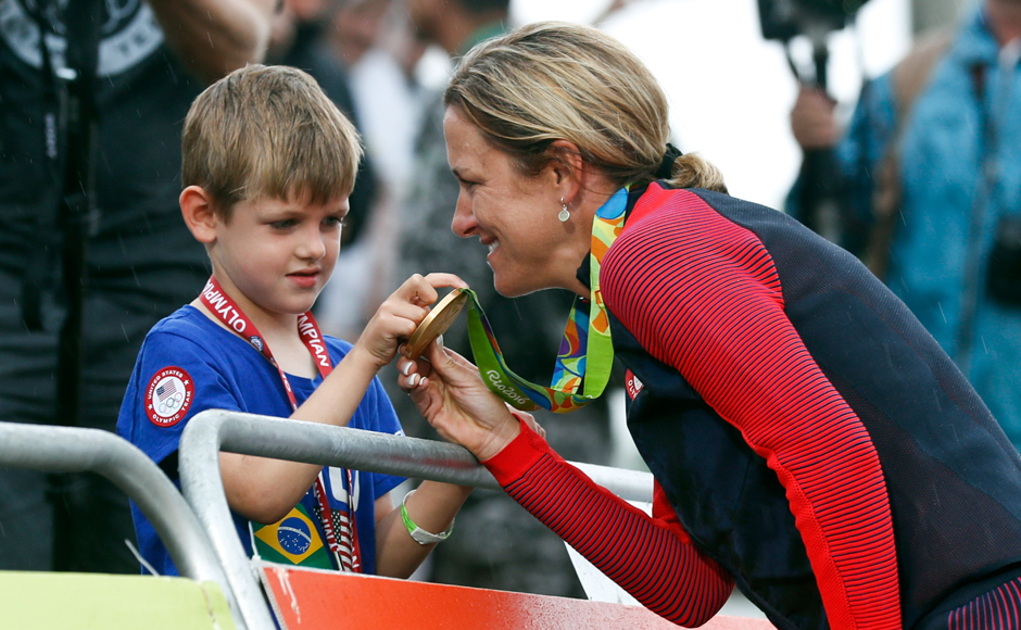 Cyclist Kristin Armstrong of the United States, right, shows her gold medal to his son Lucas William Savola after winning the women's individual time trial event at the 2016 Summer Olympics in Pontal beach, Rio de Janeiro, Brazil, Wednesday, Aug. 10, 2016. AP