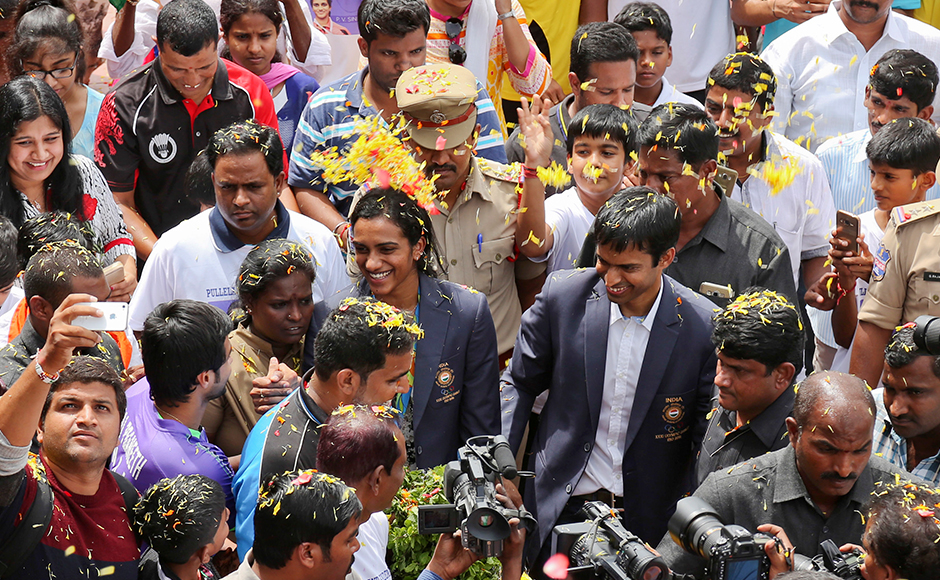 P.V. Sindhu and Pullela Gopichand are showered with flower petals during their reception at the Gopichand Academy. AP