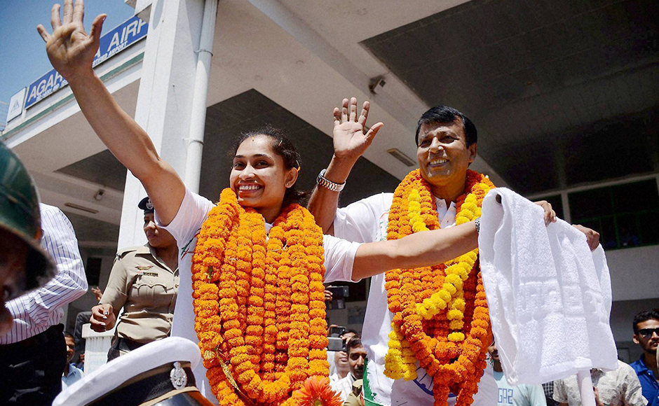 Gymnast Dipa Karmakar and her coach BS Nandi being accorded warm welcome upon their arrival at the airport in Agartala, Tripura on Monday after participating in Rio Olympics 2016. PTI