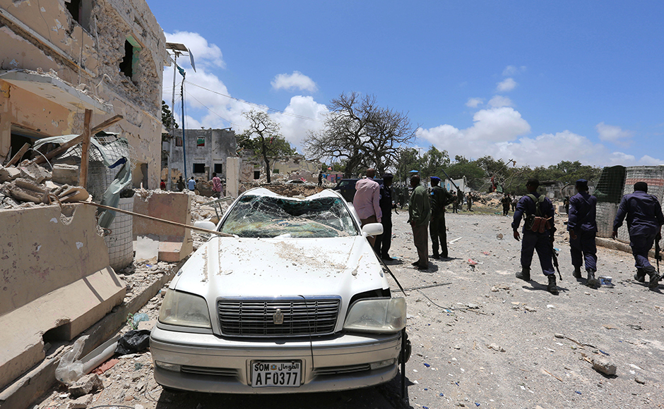 Somali government forces walk past a car destroyed as they arrive to secure the scene of a car bomb claimed by al Shabaab Islamist militants outside the president's palace in the Somali capital of Mogadishu, August 30, 2016. Reuters