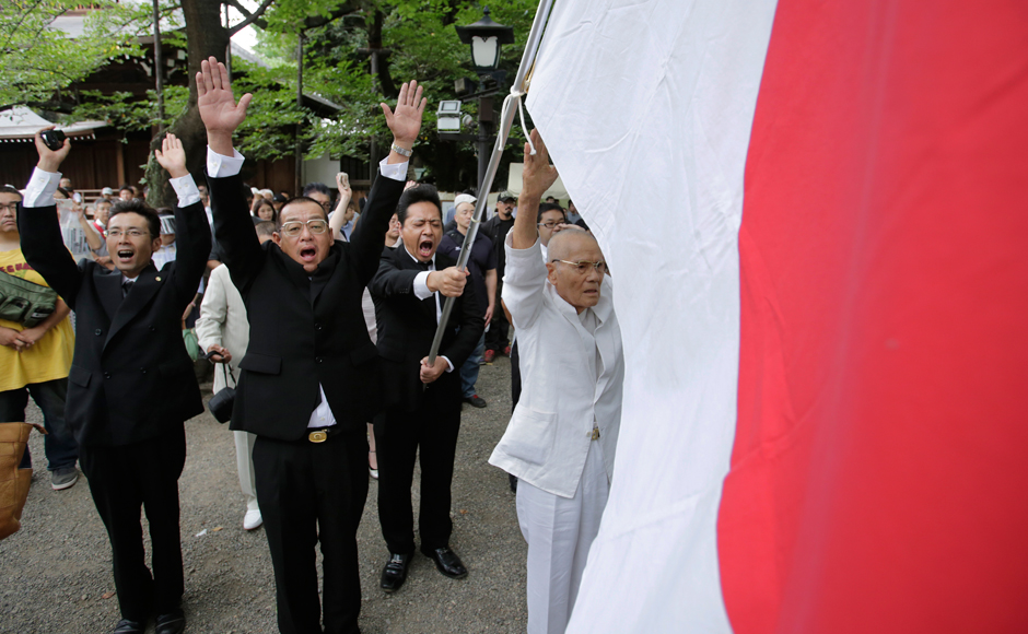 Members of a right wing group give three cheers of banzai at Yasukuni Shrine in Tokyo Monday, Aug. 15, 2016. Japan marked the 71st anniversary of the end of World War II. AP