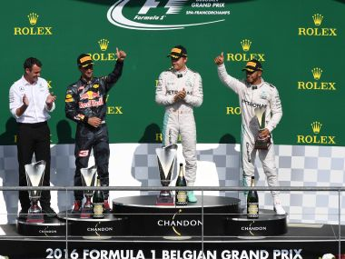 Nico Rosberg celebrates on the podium with Daniel Ricciardo and Lewis Hamilton. AP