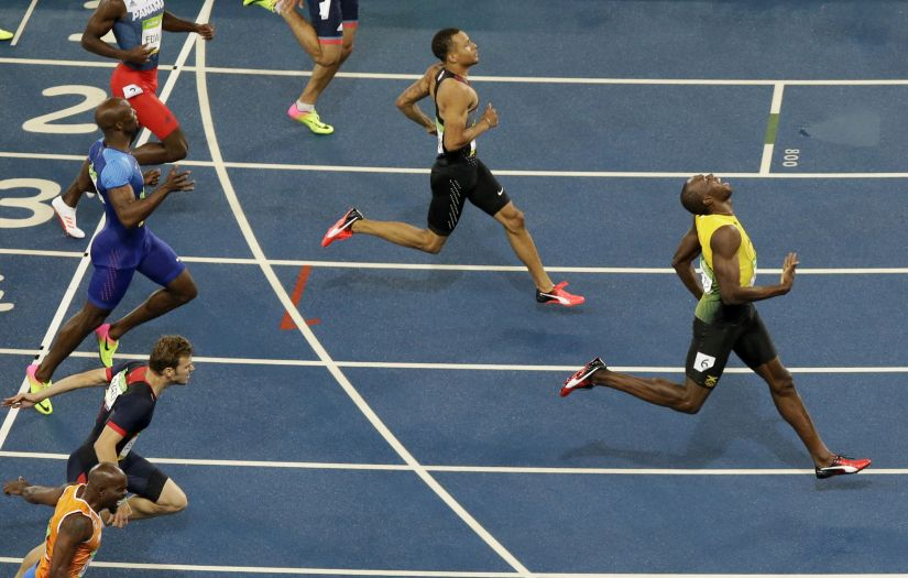 Usain Bolt from Jamaica celebrates after crossing the line to win the gold medal. AP