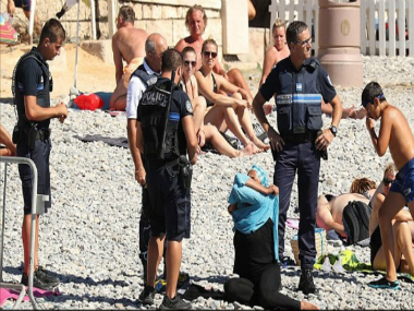 Image of the woman being asked to remove her burkini. Image Courtesy: Twitter